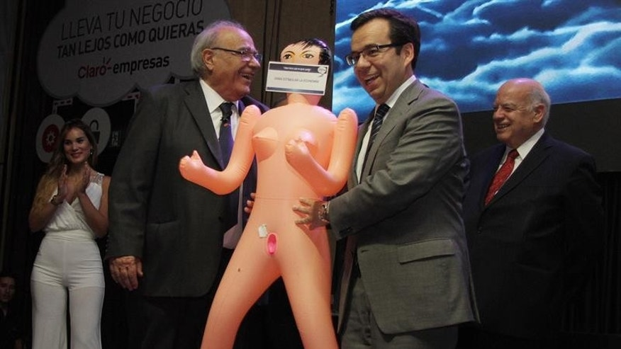 Photo provided on Dec. 14, 2016 shows Chile's Economy Minister Luis Felipe Cespedes (R), receiving a inflatable doll as a present FROM the Manufacturing Exporters Association (ASEXMA) in Santiago, Chile on Dec. 13, 2016.
