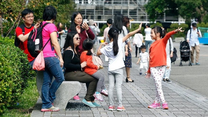 In this Sunday, Nov. 20, 2016 photo, Taiwanese people enjoy their weekend at the Sun Yat-sen Memorial Hall in Taipei, Taiwan. Taiwan will soon start mandating two-day weekends for its longsuffering workforce. The changed labor standards reflect desires for better work-life balance in this affluent, industrialized island. A new law due to be signed by President Tsai Ing-wen before the year's end requires companies to give workers two full days off per week. (AP Photo/Chiang ying-ying)