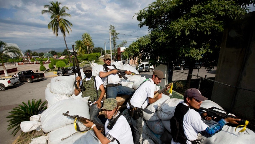 Men of the Self-Defense Council of Michoacan ride on a sandbag-filled truck while trying to flush out alleged members of The Caballeros Templarios drug cartel from the town of Nueva Italia, Mexico.
