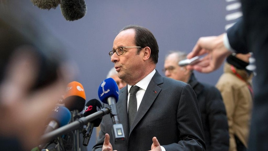 French President Francois Hollande, center, speaks with the media as he arrives for an EU Summit in Brussels on Thursday, Dec. 15, 2016. European Union leaders meet Thursday in Brussels to discuss defense, migration, the conflict in Syria and Britain's plans to leave the bloc. (AP Photo/Virginia Mayo)