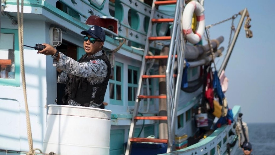 FILE - In this Friday, Dec. 9, 2016, file photo, a Thai navy officer gestures as he inspects a fishing boat in the waters off the coast of Samut Sakhon, Thailand. Thai fishing boats blocked from Indonesian waters following reports of worker abuses are now traveling thousands of miles to the western Indian Ocean to fish, but the abuses continue, Greenpeace said in a report released Thursday. (AP Photo/Dake Kang, File)