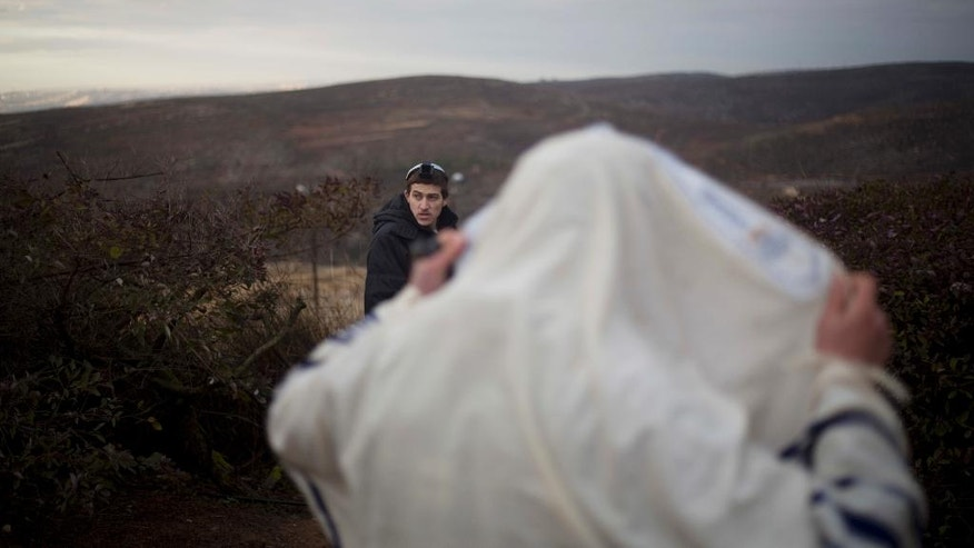 A Jewish settler covered in a prayer shawl prays in Amona, an unauthorized Israeli outpost in the West Bank, east of the Palestinian town of Ramallah, Thursday, Dec. 15, 2016. Local residents have rejected what looks to be a final compromise with the Israeli government and evacuation of the outpost in expected soon. (AP Photo/Ariel Schalit)