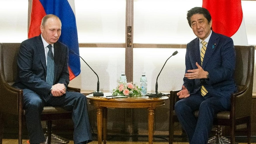 Japanese Prime Minister Shinzo Abe, right, gestures while speaking to Russian President Vladimir Putin during their meeting at a hot springs resort in Nagato, western Japan, Thursday, Dec. 15, 2016. Despite continued sanctions on Russia, Abe is eager to make progress on a 70-year-old territorial dispute that has kept their countries from signing a peace treaty formally ending World War II. (AP Photo/Alexander Zemlianichenko, pool)