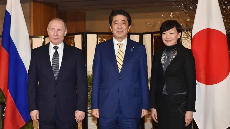 Russian President Vladimir Putin, left, poses with Japanese Prime Minister Shinzo Abe, center, and his wife, Akie, for the media upon his arrival at a hot springs resort for a meeting in Nagato, Japan, Thursday, Dec. 15, 2016. The leaders of Russia and Japan held talks on a territorial dispute that has divided their countries for 70 years. For Putin, the summit meeting marks his first official visit to a G-7 country since Russia annexed Crimea in 2014. (Kazuhiro Nogi/Pool Photo via AP)