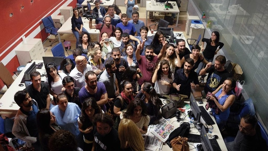 "FILE - In this file photo taken Tuesday, Oct. 4, 2016, the journalists of the IMC-TV gather in their Istanbul office after their television channel was shut down. A dozen police officers, joined by officials from Turkey's treasury and the county's broadcasting watchdog, marched into the headquarters of the pro-Kurdish IMC-TV television station, sealed off the control rooms and forced the channel off the air during a live program on democracy. Turkey has ""all but silenced independent media"" in an accelerating crackdown on journalists who are being detained on ""bogus charges"" including terrorism, an international rights group said Thursday, Dec. 15, 2016. (AP Photo/File)"