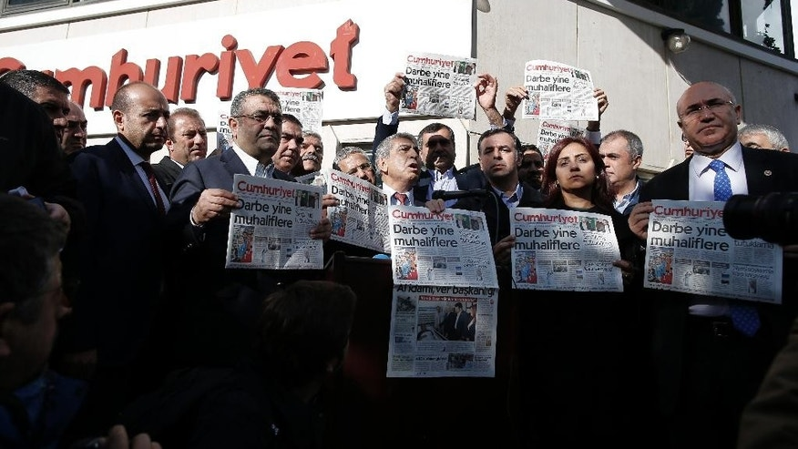 "FILE - A Monday, Oct. 31, 2016 photo from files showing journalists and lawmakers holding copies of Cumhuriyet newspaper outside its Istanbul headquarters after police detained chief editor Murat Sabuncu and two columnists of Turkey's opposition Cumhuriyet newspaper and had warrants to detain 10 other senior staff members, in Istanbul,  the state-run-Anadolu Agency reported. Turkey has ""all but silenced independent media"" in an accelerating crackdown on journalists who are being detained on ""bogus charges"" including terrorism, an international rights group said Thursday, Dec. 15, 2016. (AP Photo/Emrah Gurel, File)"