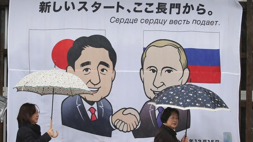 People walk in front of banner of Russian President Vladimir Putin and Japanese Prime Minister Shinzo Abe characters meeting in Nagato, western Japan, Wednesday, Dec. 14, 2016. Russia's President Vladimir Putin will visit Japan on Thursday where he will meet with Japan's Prime Minister Shinzo Abe to negotiate over a 70-year-old island dispute that has kept them from signing a peace treaty. (AP Photo/Koji Sasahara)