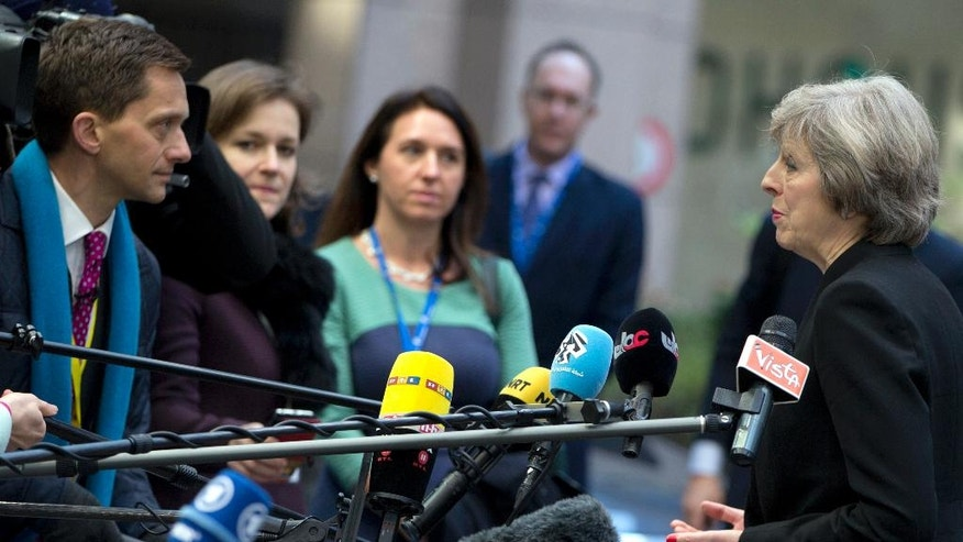 British Prime Minister Theresa May, right, speaks with the media as she arrives for an EU Summit in Brussels on Thursday, Dec. 15, 2016. European Union leaders meet Thursday in Brussels to discuss defense, migration, the conflict in Syria and Britain's plans to leave the bloc. (AP Photo/Virginia Mayo)