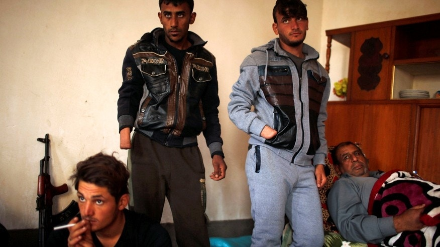 Dec. 13, 2016: Azad Hassan (second right) and his brother Mohammad, whose hands were chopped off by Islamic State militants, stand beside their wounded father in a house south of Mosul, Iraq.
