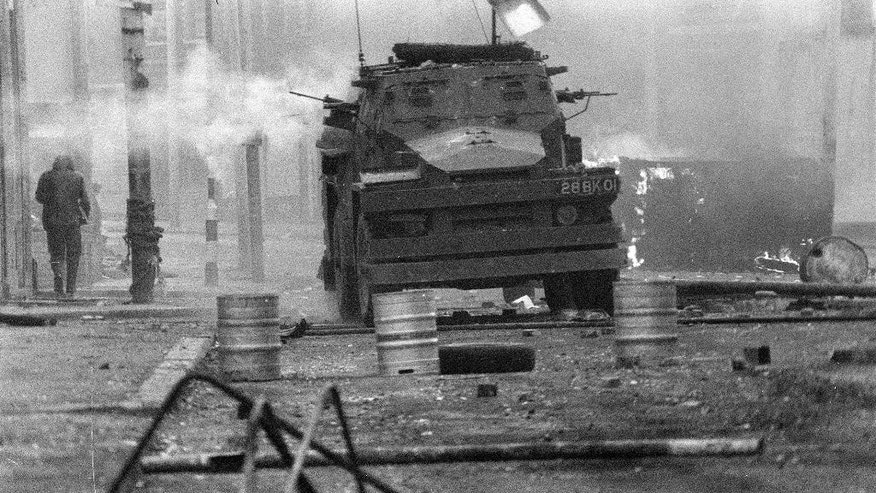 FILE - In this April 17, 1972 file photo, a British Army armoured vehicle makes its way along a barricade while on patrol in the Lower Falls area of west Belfast. Trouble in the area erupted after the shooting of Joe McCann, an IRA leader, the previous day. Belfast prosecutors say Friday Dec. 16, 2016, they will pursue murder charges against two retired British soldiers who fatally shot 25-year-old Joe McCann, a commander of the outlawed Official IRA faction. (AP Photo/Michel Lipchitz, File)
