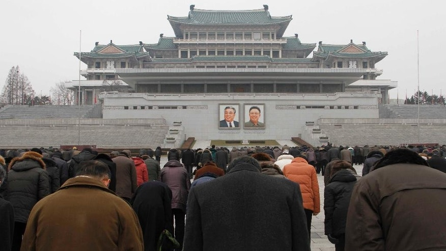 People offer three minutes of silence in front of portraits of the late leaders Kim Il Sung, left, and Kim Jong Il at the Kim Il Sung Square in Pyongyang, North Korea, Saturday, Dec. 17, 2016, to mark the fifth anniversary of Kim Jong Il's death. It's been five years since North Korean leader Kim Jong Un took power following the death of his father, Kim Jong Il, whose demise was observed at monuments and on city center plazas across the nation Saturday. (AP Photo/Kim Kwang Hyon)