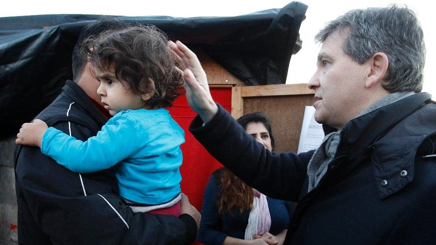 Leftist contender for the Socialist primary election Arnaud Montebourg, right, talks with a family coming from Iraq during a visit at a migrants camp built by Doctors Without Borders in Grande Synthe, outside Dunkirk, northern France, Wednesday, Dec. 14, 2016. (AP Photo/Michel Spingler)