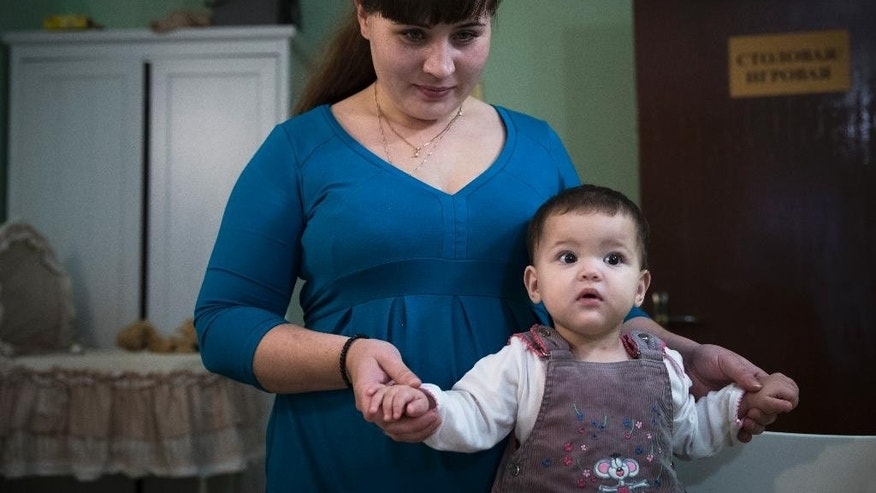 In this photo taken on Friday, Oct. 7, 2016, Lilya Rakheyeva and her daughter Anyuta pose for a photo at an Orthodox Christian emergency shelter in Moscow, Russia. The Russian Orthodox Church is expanding its influence in what was once an officially godless state _ and President Vladimir Putin appears eager to harness that resurgent power of faith to promote his own agenda. (AP Photo/Pavel Golovkin)