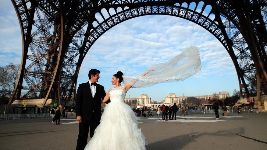Rodrigo and Nancy of Mexico pose for a photographer under the Eiffel Tower as they are on honeymoon in Paris, Friday, Dec. 16, 2016. (AP Photo/Christophe Ena)