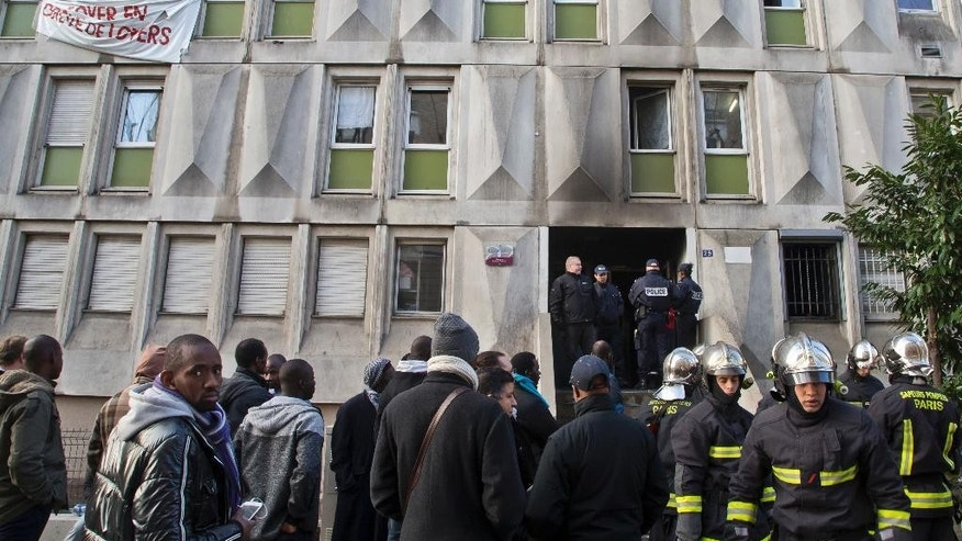 Migrants and fire fighters gather outside a migrant workers' center after a fire broke out in Bouglogne-Billancourt, west of Paris, Friday, Dec. 16, 2016. French police are investigating a fire that broke in a migrant workers' center near Paris and left two people seriously injured. (AP Photo/Michel Euler)