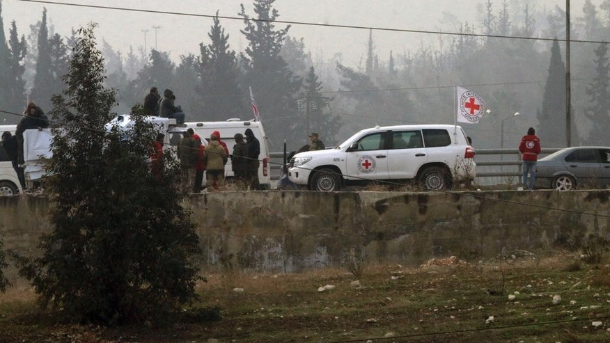 In this photo released by the Syrian official news agency SANA, civilians gather near the Red Cross vehicles for evacuation from eastern Aleppo, Syria, Friday, Dec. 16, 2016. The Syrian government suspended evacuations from eastern Aleppo just hours after they resumed on Friday, saying that rebels had opened fire on a convoy of evacuees at a crossing point with the enclave, state TV reported. (SANA via AP)