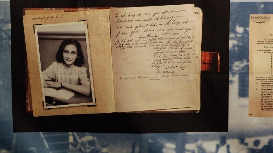 "FILE - This June 12, 2009 file photo, shows a photo of Anne Frank at the opening of the exhibition: ""Anne Frank, a History for Today"", at the Westerbork Remembrance Centre in Hooghalen, northeast Netherlands. A new study by the Anne Frank House museum in Amsterdam said Friday, Dec. 16, 2016, there is no conclusive evidence that the Jewish diarist and her family were betrayed to the Netherlands' German occupiers during World War II, leading to their arrest and deportation. (AP Photo/Bas Czerwinski, File)"