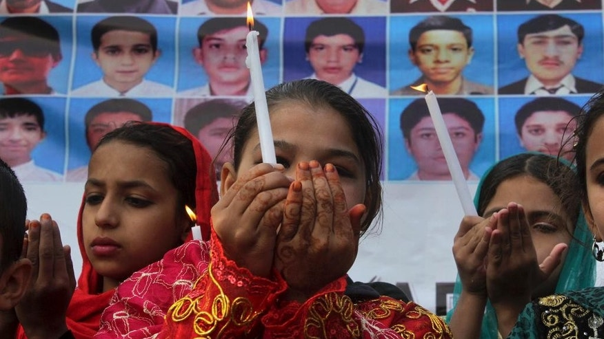 Pakistani children hold candles and pray for victims of an attack on a Peshawar school in 2014, during a ceremony to mark second anniversary of the attack, in Peshawar, Pakistan, Friday, Dec. 16, 2016. Pakistani Taliban militants attacked an army-run school in Peshawar, killing more than 150 people, mostly children, on Dec. 16. 2014. (AP Photo/Muhammad Sajjad)