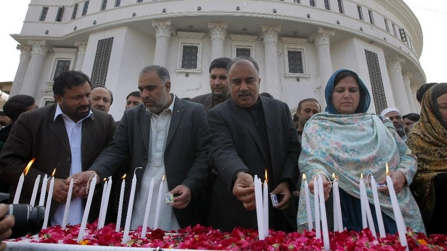 Pakistani lawmakers from provincial Khyber Pakhtunkhwa assembly light candle during a ceremony to mark second anniversary of the attack on a Peshawar school in 2014, in Peshawar, Pakistan, Friday, Dec. 16, 2016. Pakistani Taliban militants attacked an army-run school in Peshawar, killing more than 150 people, mostly children, on Dec. 16. 2014. (AP Photo/Muhammad Sajjad)