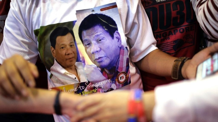 A Filipino supporter wears a t-shirt with pictures of Philippine President Rodrigo Duterte printed on it as she waits to meet him in Singapore on Friday, Dec. 16, 2016.(AP Photo/Wong Maye-E)