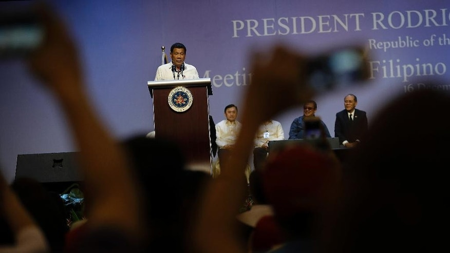 Philippine President Rodrigo Duterte addresses the Filipino community in Singapore as they listen and cheer, some taking photos with their smart phones during his speech on Friday, Dec. 16, 2016. (AP Photo/Wong Maye-E)
