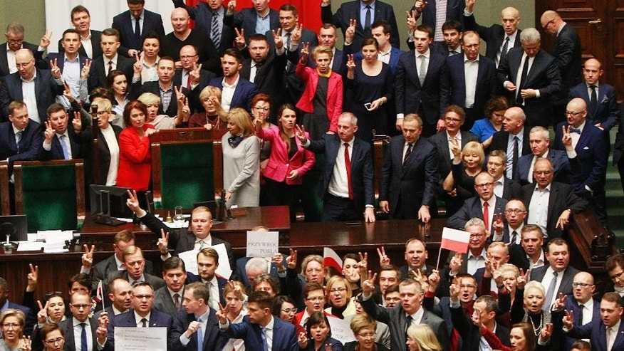Opposition lawmakers occupy the podium to protest in the lower house of parliament in Warsaw, Poland, on Friday, 16 Dec. 2016. They protested in a large group around the podium against the ruling party pans to limit reporters' access to lawmakers. (AP Photo/Czarek Sokolowski)