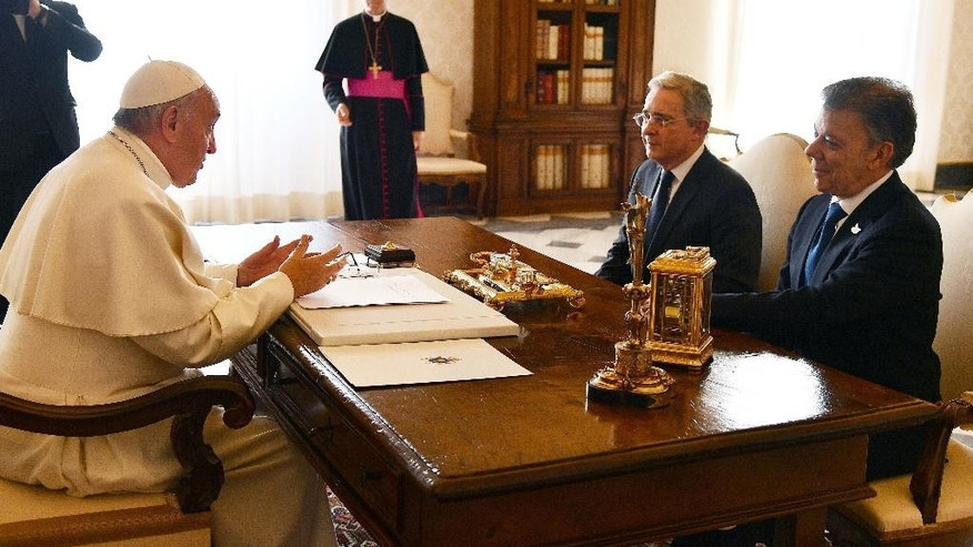 Pope Francis talks to Colombian President Juan Manuel Santos, right, and former President Alvaro Uribe during a meeting at the Vatican, Friday, Dec. 16, 2016. (Vincenzo Pinto /Pool Photo via AP)