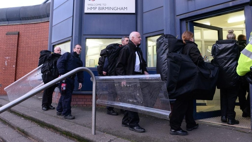 Security staff carry equipment into HMP Birmingham, in Birmingham, England, Friday, Dec. 16, 2016. Security firm G4S, which runs HMP Birmingham, has deployed a specialist riot squad to a prison the English city of Birmingham after disturbances by inmates spread to four wings of the facility. The disturbance began at about 9 a.m. GMT (0400 a.m. EST) Friday. The unrest comes at a time that Britain's prisons are under intense pressure. Members of the Prison Officers Association say violence and inmate suicides are rising. (Joe Giddens/PA via AP)