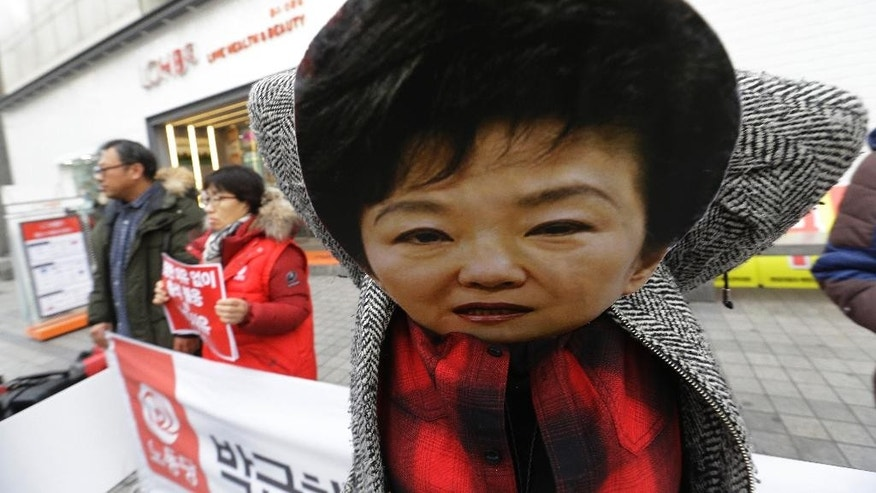 A protester wears a mask of impeached South Korean President Park Geun-hye during a rally demanding the arrest of Park in Seoul, South Korea, Monday, Dec. 12, 2016. South Korean prosecutors said Sunday that they have indicted a former senior aide to Park in their investigation into the massive political scandal that led to Park's downfall, local media reported.(AP Photo/Ahn Young-joon)