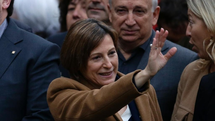 The president of the Catalonia region's parliament, Carme Forcadell waves to the crowd surrounded by pro-independence mayors and other elected officials on Friday, Dec. 16, 2016 in Barcelona, Spain, as she walks towards a court to testify for allowing lawmakers to debate earlier this year on the region's secession from Spain. Puigdemont plans to go ahead with a new referendum on independence by September despite a ruling by Spain's Constitutional Court banning the vote. (AP Photo/Manu Fernandez)