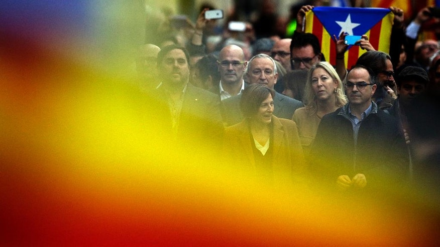 The president of the Catalonia region's parliament, Carme Forcadell, center, is surrounded by pro-independence mayors and other elected officials on Friday, Dec. 16, 2016 in Barcelona, Spain, as she walks towards a court to testify for allowing lawmakers to debate earlier this year on the region's secession from Spain. Puigdemont plans to go ahead with a new referendum on independence by September despite a ruling by Spain's Constitutional Court banning the vote. (AP Photo/Manu Fernandez)