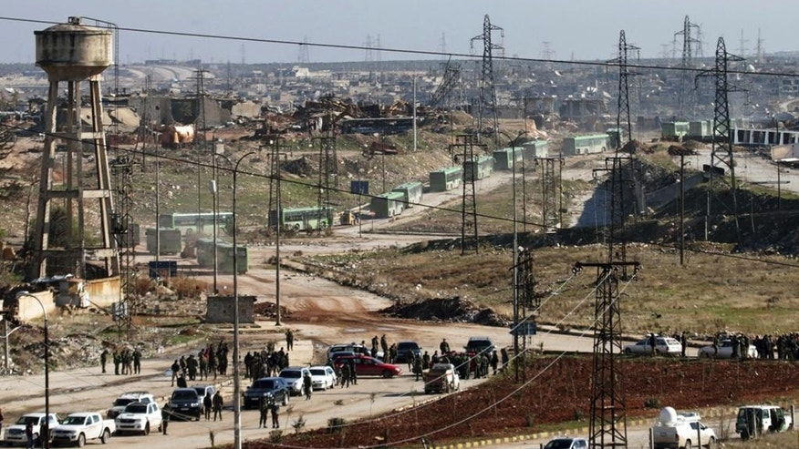 In this photo released by the Syrian official news agency SANA, green government buses carrying residents evacuating from eastern Aleppo, Syria, Thursday, Dec. 15, 2016.  The Russian military said over 1,000 people have been evacuated from Aleppo under a cease-fire deal reached with Syrian rebels. France's ambassador to the United Nations says international observers should monitor the safe evacuation of civilians and fighters from the war-torn Syrian city of Aleppo. (SANA via AP)
