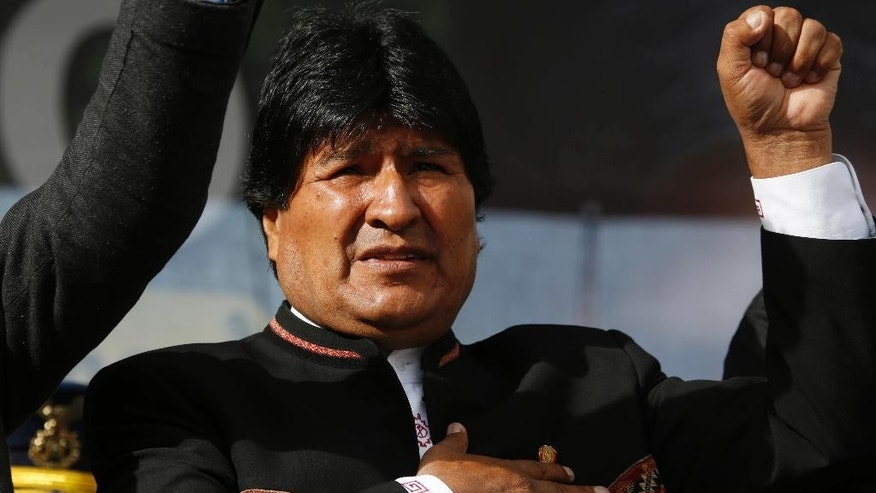 FILE - In this Feb. 22, 2016, file photo, Bolivia's President Evo Morales sings his national anthem at a signing ceremony for the expansion of a road that connects the capital with the nearby city of El Alto, in La Paz, Bolivia. Morales accepted on Saturday, Dec. 17, 2016 to run for a fourth term in office after his ruling party proclaimed him its candidate in 2019 elections, defying the results of a February referendum. (AP Photo/Juan Karita, File)