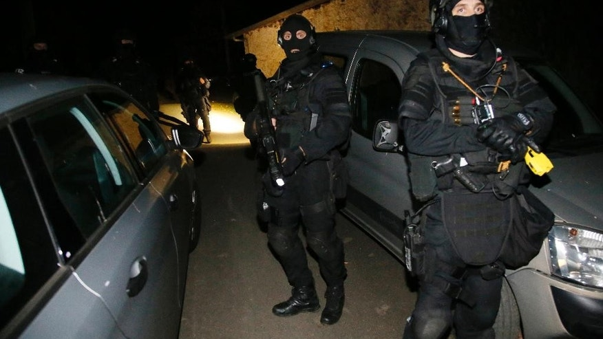 French police officers stand outside a villa during a search operation in Louhossoa, southwestern France, Friday, Dec. 16, 2016, targeting the Basque separatist group ETA. (AP Photo/Bob Edme)