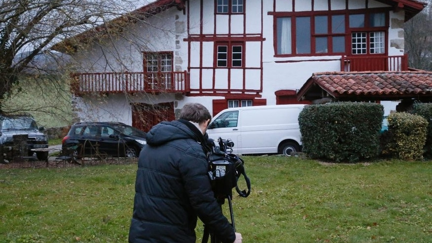 A cameraman films a house where arrests of Basque activists took place late Friday night in Louhossoa, southern France, Saturday, Dec. 17, 2016. Spain's Interior Ministry says Spanish and French police have made three arrests upon discovering a suspected weapons trove for the Basque militant group ETA in southern France. (AP Photo/Bob Edme)