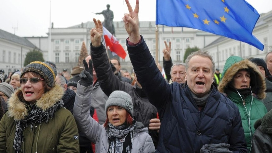 Protesters sing Poland's national anthemn during an anti-government demonstration, in Warsaw, Poland, Saturday, Dec. 17, 2016. Opponents of the country's populist government are staging a new protest outside the presidential palace in an appeal to the head of state to protect the young democracy's constitutional order from a series of government steps they deem anti-democratic. (AP Photo/Alik Keplicz)