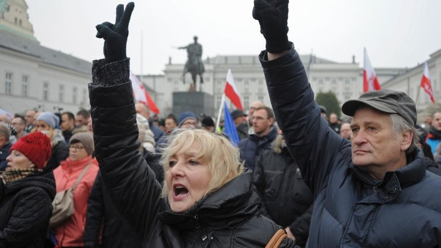 Protesters shout slogans during an anti-government demonstration, in Warsaw, Poland, Saturday, Dec. 17, 2016. Opponents of the country's populist government are staging a new protest outside the presidential palace in an appeal to the head of state to protect the young democracy's constitutional order from a series of government steps they deem anti-democratic. (AP Photo/Alik Keplicz)