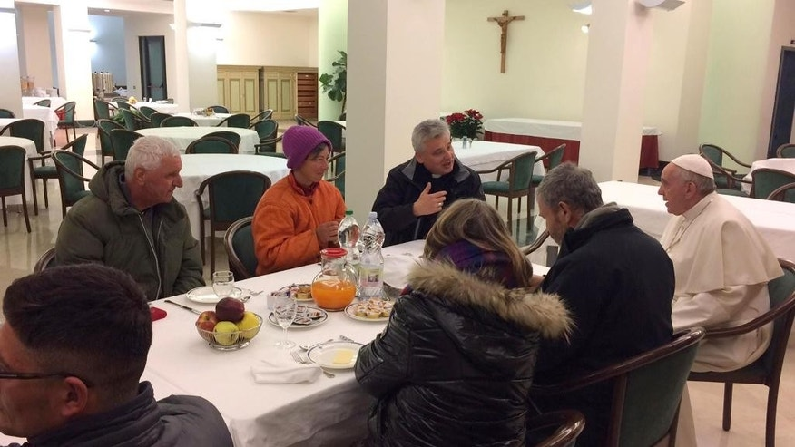 Pope Francis, right, flanked at right by Mons. Konrad Krajewski, celebrates his 80th birthday sharing a breakfast with homeless people before celebrating Mass with cardinals at the Vatican, Saturday Dec. 17, 2016. The Vatican said that the pope chatted early Saturday with each of the homeless guests, four Italians, two Romanians, a Moldovan, two Romanians and a Peruvian, and shared with them Argentinian cakes before heading to Mass.  (L'Osservatore Romano/pool photo via AP)
