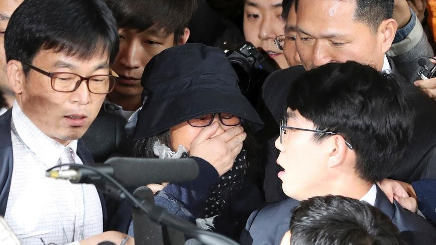 FILE - In this Oct. 31, 2016 file photo, Choi Soon-sil, center, a longtime friend of South Korean President Park Geun-hye, arrives at the Seoul Central District Prosecutors' Office in Seoul, South Korea. The jailed confidante of the disgraced president begins a trial Monday, Dec. 19 that will explore a scandal that led to Park's impeachment after millions took to the streets in protest. (AP Photo/Lee Jin-man, File)