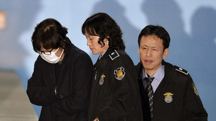 FILE - In this Nov. 3, 2016 file photo, Choi Soon-sil, a longtime friend of South Korean President Park Geun-hye, left, is escorted to get on a bus of Ministry of Justice as she leaves the Seoul Central District Court in Seoul, South Korea. The jailed confidante of the disgraced president begins a trial Monday, Dec. 19, that will explore a scandal that led to Park's impeachment after millions took to the streets in protest. (Korea Pool via AP, File)