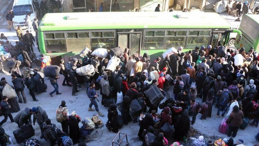 This image released on Thursday, Dec. 15, 2016 by Aleppo 24, shows residents gathered near a green government bus as they hold their belongings for evacuation from eastern Aleppo, Syria. As the last holdouts leave the rebel-held enclave in Aleppo, they speak of their love for the city despite witnessing so much destruction and death. Bit by bit over three weeks, the government offensive chipped away at their last refuge. (Aleppo 24 via AP)