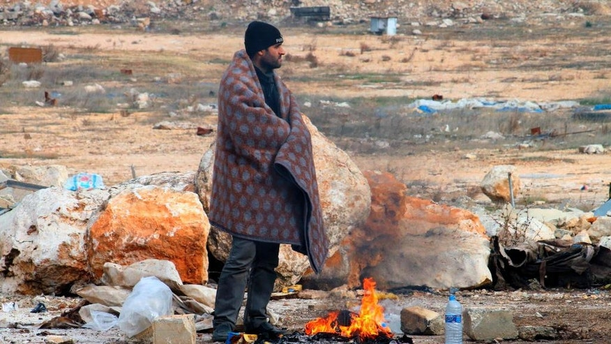 This image released on Friday, Dec. 16, 2016 by Aleppo 24, shows a man of eastern Aleppo standing next to a fire in western rural Aleppo, Syria. As the last holdouts leave the rebel-held enclave in Aleppo, they speak of their love for the city despite witnessing so much destruction and death. Bit by bit over three weeks, the government offensive chipped away at their last refuge. (Aleppo 24 via AP)
