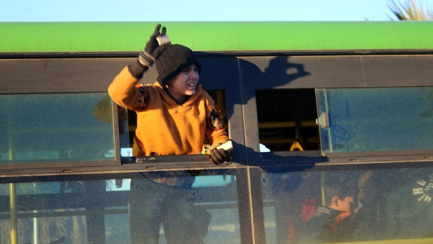 This image released on Thursday, Dec. 15, 2016 by Aleppo 24, shows a boy standing inside a green government bus, while arriving in western rural Aleppo, Syria, as part of an evacuation deal. As the last holdouts leave the rebel-held enclave in Aleppo, they speak of their love for the city despite witnessing so much destruction and death. Bit by bit over three weeks, the government offensive chipped away at their last refuge. (Aleppo 24 via AP)