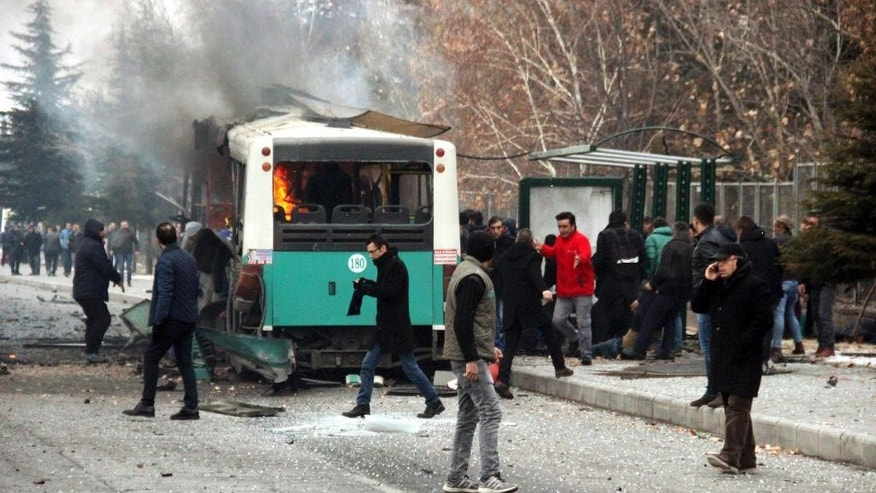 A public bus is burning at the scene of a car bomb attack in central Anatolian city of Kayseri, Turkey, Saturday, Dec. 17, 2016. A public bus was heavily damaged and dear and injured were reported. Turkish authorities have banned distribution of images relating to the Istanbul explosions within Turkey. (IHA via AP)