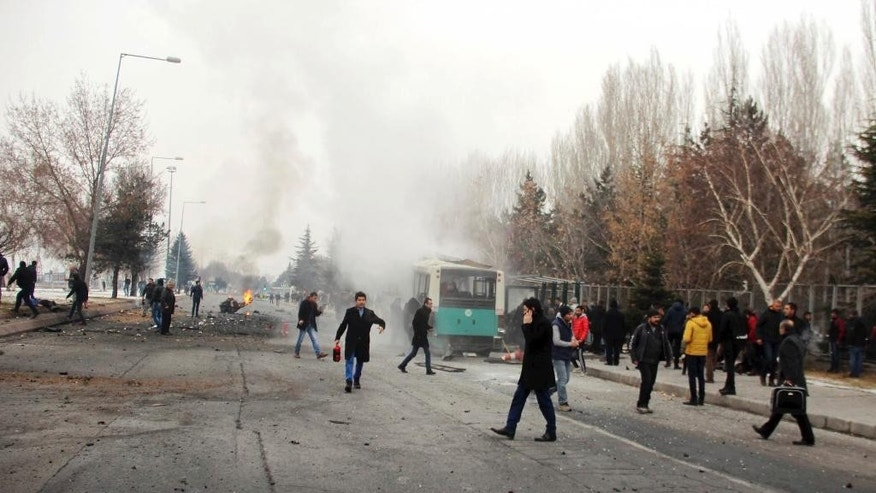 Rescue services members work at the scene of a car bomb attack in central Anatolian city of Kayseri, Turkey, Saturday, Dec. 17, 2016. A public bus was heavily damaged and dear and injured were reported. Turkish authorities have banned distribution of images relating to the Istanbul explosions within Turkey. (IHA via AP)