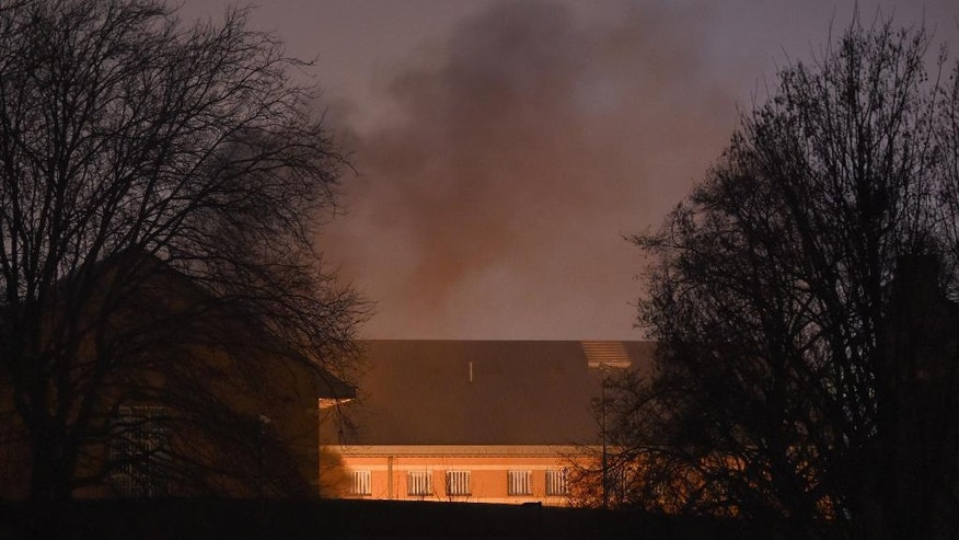 Smoke rises above HMP Birmingham, in Birmingham, England, Friday, Dec. 16, 2016. Security firm G4S, which runs HMP Birmingham, has deployed a specialist riot squad to a prison the English city of Birmingham after disturbances by inmates spread to four wings of the facility. The disturbance began at about 9 a.m. GMT (0400 a.m. EST) Friday. The unrest comes at a time that Britain's prisons are under intense pressure. Members of the Prison Officers Association say violence and inmate suicides are rising. (Joe Giddens/PA via AP)
