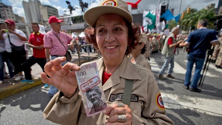 "A member of the Venezuelan militia shows a sample of a banknote with the image of opposition leader and President of National Assembly Henry Ramos Allup and a sign that reads in Spanish "" out of circulation,"" during a rally in Caracas, Venezuela, Saturday, Dec. 17, 2016. Venezuela's President Nicolas Maduro called for a pro-government rally as the country to give a tribute to the Venezuelan hero Simon Bolivar meanwhile the country is on edge over his so-far failed plan to introduce larger-denominated bills to fight soaring inflation. (AP Photo/Fernando Llano)"