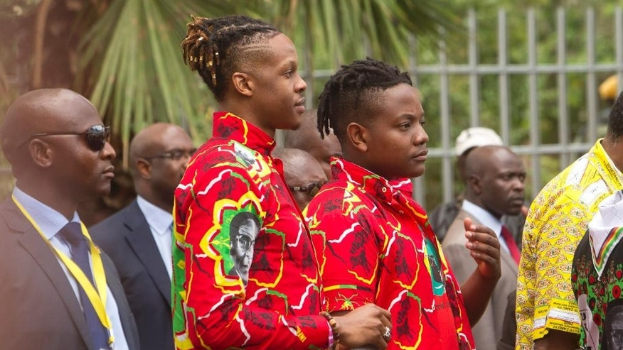 Zimbabwean President Robert Mugabe's children Robert, left, and Chatunga attend Zanu PF's 16th Annual Peoples Conference in Masvingo, about 300 kilometres south of the capital Harare, Saturday, Dec. 17, 2016. Mugabe officially opened the conference where he is set to be endorsed as the ruling party candidate for Presidential elections set for 2018.(AP Photo/Tsvangirayi Mukwazhi)