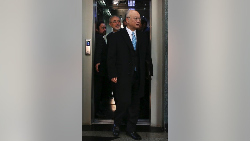 Director General of the International Atomic Energy Agency, IAEA, Yukiya Amano and chief of Iran's Atomic Energy Organization Ali Akbar Salehi, rear center, arrive for a news briefing after their meeting in Tehran, Iran, Sunday, Dec. 18, 2016. (AP Photo/Vahid Salemi)