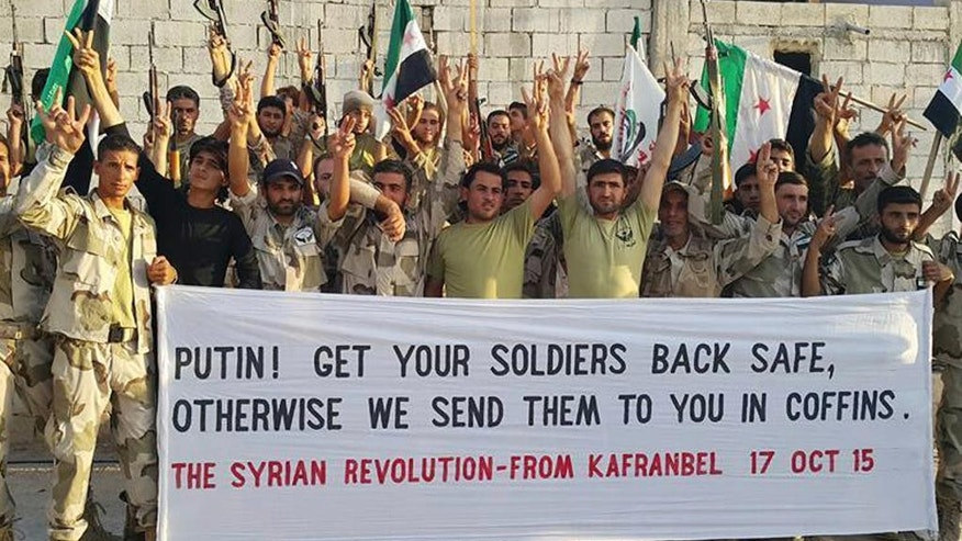 FILE - In this file photo released on October 17, 2015, and provided by the Fursan al-Haq Syrian rebel brigade, which has been authenticated based on its contents and other AP reporting, Free Syrian Army fighters of Fursan al-Haq Brigade hold a banner, in Kafranbel, Idlib province, northern Syria. The battle for Aleppo has gripped the world, but it is hardly the only active front across Syria. One of the next targets for the forces of Bashar Assad will probably be the heartland of rebel territory, the neighboring Idlib province. (Fursan al-haq Rebel Brigade via AP, File)